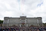 The Red Arrows display team perform a fly-past as members of the royal family stand together on the balcony at Buckingham Palace following the Queen's Birthday parade, on June 15, 2013