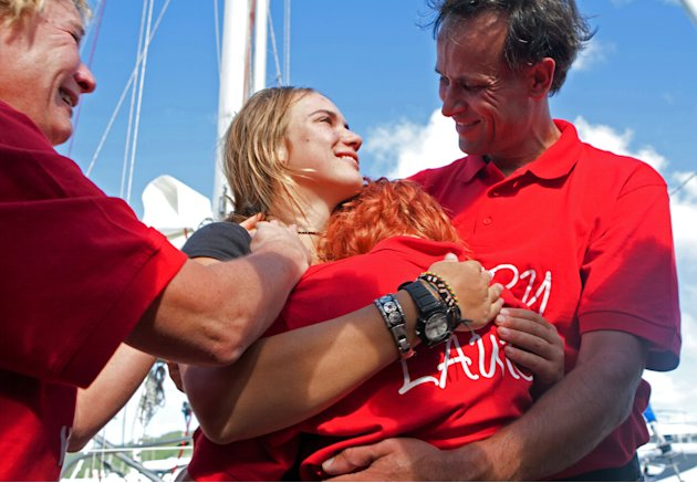 Dutch sailor Laura Dekker, center left, is hugged by her father Dick Dekker, right, sister Kim Dekker, center right, and mother Babs Muller, left, after arriving to Simpson Bay, St. Maarten, Saturday