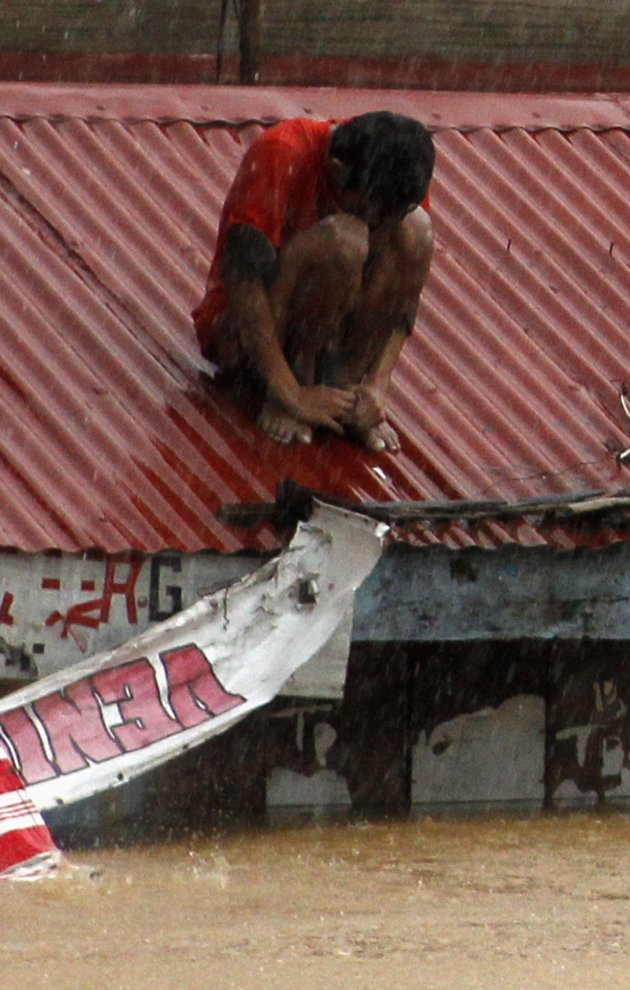 A man waits for rescuers on the rooftop of a house swamped with floodwaters in Marikina, Metro Manila August 7, 2012.
