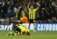 Dortmund's Marco Reus and Marcel Schmelzer, react, after the Champions League semifinal second leg soccer match between Real Madrid and Borussia Dortmund at the Santiago Bernabeu stadium in Madrid, Spain, Tuesday, April 30, 2013. (AP Photo/Andres Kudacki)