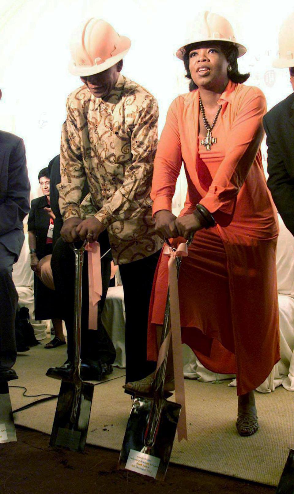 FILE - In this Dec. 6, 2002 file photo, former South African President Nelson Mandela, left, and American talk show host Oprah Winfrey participate in a ground breaking ceremony for the Oprah Winfrey Leadership Academy for Girls in Meyerton, South Africa. Heroic in his deeds, graceful in his manner, sainted in his image, Nelson Mandela long served as both cause and muse in the entertainment community. From the 1960s, when he was a political prisoner and South Africa was under the laws of apartheid, right up to recent times, when the racist laws of the land had fallen and he was among the world's most admired people, Mandela inspired concerts, songs, poems, fiction and movies. (AP Photo/Themba Hadebe, File)