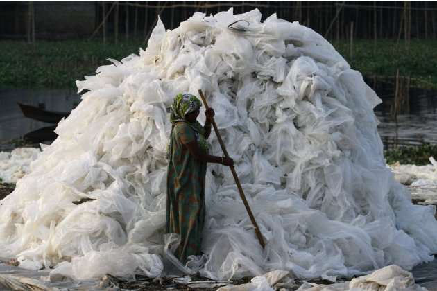 Woman dries used polythene sheets after washing them on the bank of the river Buriganga in Dhaka