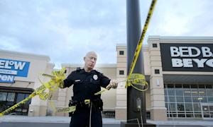 A Waco police officer takes down crime scene tape, …