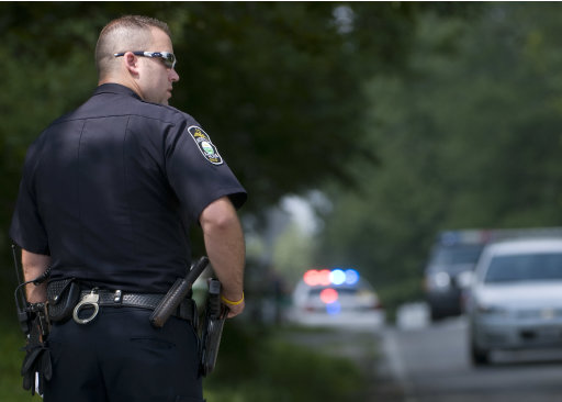 A Fairlawn, Ohio, policeman maintains traffic around a police barrier near a multiple death shooting in Copley, Ohio, Sunday, Aug. 7. 2011. A family argument in the Akron suburb ended in the shooting deaths of eight people in two places, including an 11-year-old, and two more people were wounded, authorities said Sunday (AP Photo/Phil Long)