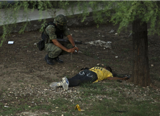 EDS. NOTE GRAPHIC CONTENT - A Mexican army soldier takes a photo of a dead man after a gun battle between army soldiers and gunmen in the northern city of Monterrey, Mexico Wednesday July 13, 2011. According to local media, the gunmen ran into a perimeter being secured by army and state police and a firefight ensued, leaving all 4 gunmen dead. Four assault rifles and a 9mm handgun were seized. (AP Photo/Hans Maximo Musielik)