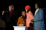 President Barack Obama, first lady Michelle Obama and their daughters Sasha, second from left, and Malia react as the girls flip the switch to light the National Christmas Tree during the 90th ...