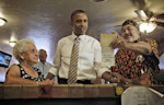 President Barack Obama is shown an old photograph by Robert Romero, owner of Romero's Cafe and Catering, right, Thursday, Aug. 9, 2012, in Pueblo, Colo. Also at the counter with Obama Virginia ...