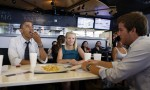 U.S. President Barack Obama reaches for some fries as he holds a round table with first time voters at OMG Burger in Miami, Florida