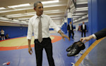 President Barack Obama is handed his shoes by a member of his staff during his visit to the U.S. Olympic Training center, Thursday, Aug. 9, 2012 in Colorado Springs, Colo. Obama had taken off his ...