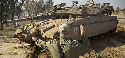 An Israeli soldier directs a tank near Kibbutz Niram, in southern Israel, Sunday, Dec. 28, 2008. Israel's Cabinet authorized a callup of thousands of reserves soldiers, suggesting plans to expand a campaign against Gaza rocket squads that has already killed some 280 Palestinians. (AP Photo/Bernat Armangue)