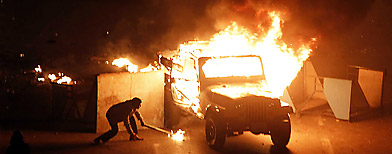 A police vehicle is set on fire by anti-government demonstrators in Cairo (AP/Xinhua, Cai Yang)