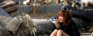 A woman reacts amidst debris caused by Friday's massive earthquake and the ensuing tsunami, in Natori. (AP/Asahi Shimbun, Toshiyuki Tsunenari)