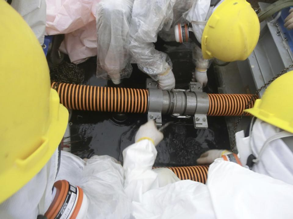 Workers wearing protective suits and masks are seen working at a site where radioactive water leaked at Tokyo Electric Power Co's (TEPCO) Fukushima Daiichi nuclear power plant in Fukushima prefecture