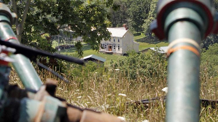 FILE - This July 27, 2011 file photo shows a farmhouse in the background framed by pipes connecting pumps where the hydraulic fracturing process in the Marcellus Shale layer to release natural gas was underway at a Range Resources site in Claysville, Pa. In Pennsylvania's fracking boom, new and more unconventional wells leaked far more than older and traditional wells, according to a study of inspections of more than 41,000 wells drilled. And that means that that methane leaks could be a problem for drilling across the nation, said the author of the study, which funded in part by environmental activist groups and criticized by the energy industry. The study was published Monday by the Proceedings of the National Academy of Sciences. (AP Photo/Keith Srakocic, File)