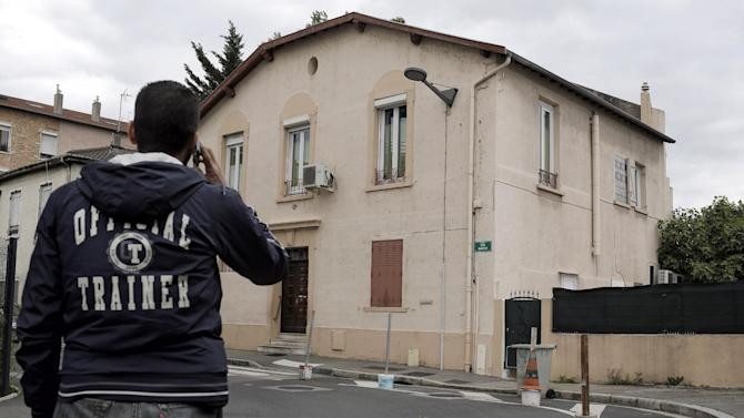 FILE - In this file photo dated Tuesday, May 26, 2015 a man makes a phone call as he walk past a mosque in Oullins outside Lyon, central France. The mosque won an unusual case last week against a Salafi worshipper taken to court after months of tension. The case was thought to be the first in France by Muslims against a Muslim invoking a 1905 law to guarantee secularism _ used by the government to pass bans on headscarves and face-covering veils. (AP Photo/Laurent Cipriani, File)