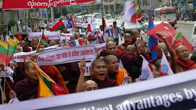 Buddhist monks holding placards shout slogans as they march for a protest Wednesday, Feb. 11, 2015, in Yangon, Myanmar. Hundreds of people have demonstrated in Yangon, Myanmar's biggest city, to protest a government decision to allow people without full citizenship, including members of the Rohingya ethnic minority, to vote in an upcoming constitutional referendum. Parliament recently decided to allow temporary identity card holders, known as white card holders, the right to vote in a referendum for constitutional amendments. (AP Photo/Khin Maung Win)