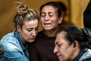 A family mourns in an area allocated for families of…