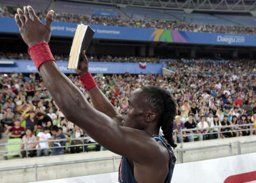 USA's Will Claye holds a bible after winning the bronze medal in the Men's Triple Jump final at the World Athletics Championships in Daegu, South Korea, Sunday, Sept. 4, 2011.  (AP Photo/David J. Phillip)