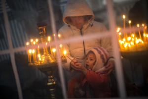 A boy is helped by his mother to light a candle inside …