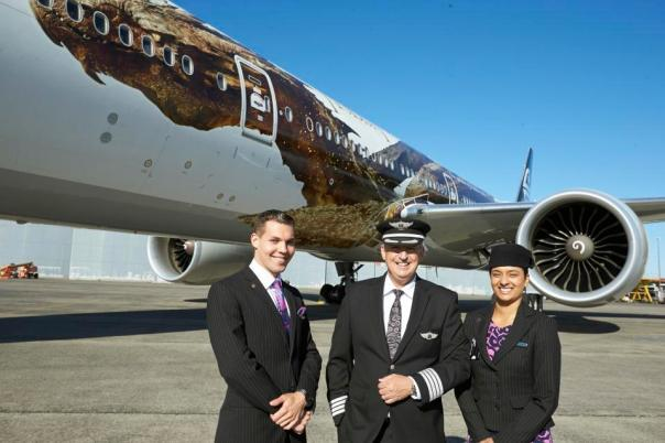 "In this photo released by Air New Zealand, Air New Zealand crew members Maxence Cherri, left, Priyanka Girish, right, and captain David Morgan, center, stand in front of a plane with an image of the dragon Smaug from Peter Jackson's Hobbit trilogy, on Monday, Dec. 2, 2013, in Auckland, New Zealand. The image was unveiled to celebrate the premiere of ""The Hobbit: The Desolation of Smaug,"" which screens Monday in Los Angeles. (AP Photo/Air New Zealand)"