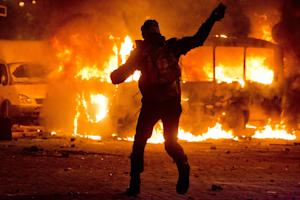 A protester throws a stone towards a burning police …
