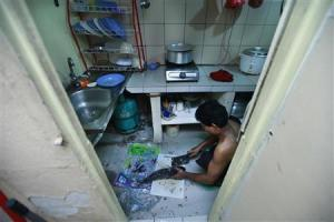 A Rohingya man cuts a fish at his rented house in Cheras …