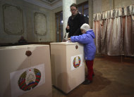 A Belarusian woman with a child casts her ballot paper at a polling station during parliamentary elections in Minsk, Belarus, Sunday, Sept. 23, 2012. Belarus is holding parliamentary elections Sunday without the main opposition parties, which boycotted the vote to protest the detention of political prisoners and opportunities for election fraud. (AP Photo/ Dmitry Brushko)