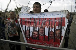 A man holds a poster behind barbed wire as riot policemen…