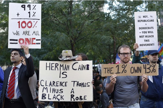 Occupy Wall Street campaign demonstrators hold placards Zuccotti Park