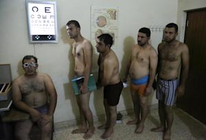 Iraqi men line up for physical examinations at the …