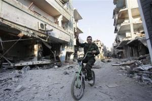 A Shi'ite fighter rides his bicycle on a damaged street…