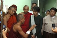In this photo taken Thursday, Nov 29, 2012, opposition leader Aung San Suu Kyi , in green, listens to a injured Buddhist monks who suffered burn injuries when security forces cracked down protesters in a hospital in Monywa, northwestern Myanmar. Opposition leader Suu Kyi is urging a negotiated resolution to protests over a military-backed copper mine in northwestern Myanmar after the government's biggest crackdown on demonstrators since reformist President Thein Sein took office last year. (AP Photo)