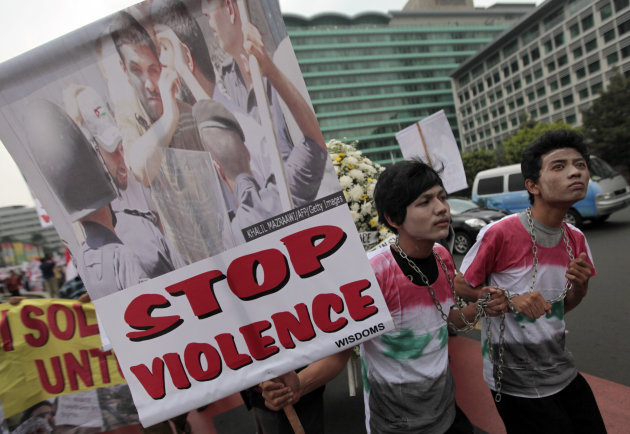 An Indonesian activist holds a poster during a protest against the government's crackdown on protests in Syria, in Jakarta, Indonesia, Friday, Oct. 28, 2011. (AP Photo/Dita Alangkara)