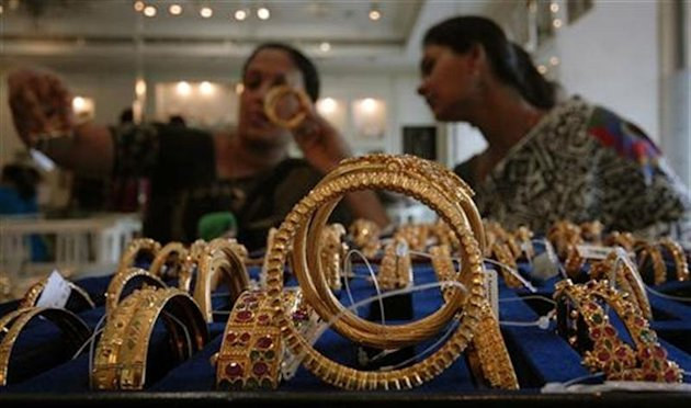 Customers look at gold bangles inside jewellery shop in Hyderabad