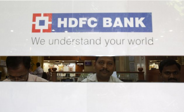 Tellers are seen through a cheque deposit counter at an HDFC bank branch in Mumbai