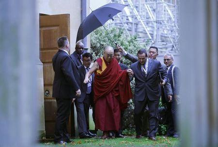 , the Dalai Lama leaves after a news conference at Magdalene College ...