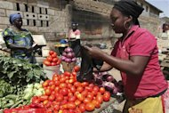 A woman sells tomatoes at a roadside grocery stall in Nigeria's central city of Jos March 9, 2010. REUTERS/Akintunde Akinleye