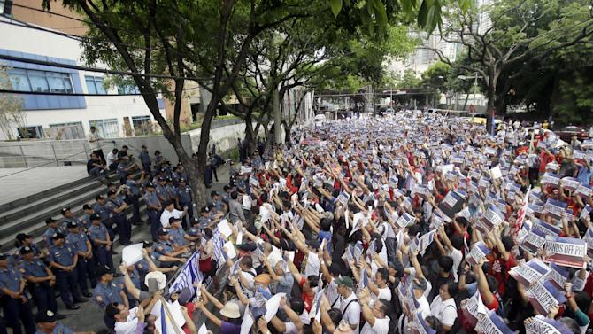 Protesters face the Chinese Consulate to display their anti-Chinese message during a Philippines Independence Day rally in the financial district of Makati city east of Manila, Philippines, Friday, June 12, 2015. The protesters condemned the recent reclamation of land by China in the disputed Spratlys group of islands on the South China Sea. (AP Photo/Bullit Marquez)