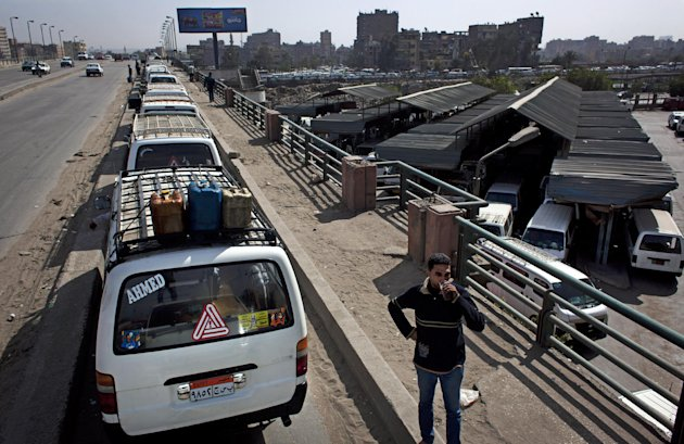 An Egyptian public transportation driver drinks tea as he stands in front of vehicles parked due to fuel shortage at a bus station, on the outskirts of Cairo, Egypt, Monday, March 11, 2013. On Sunday, drivers of Cairo's popular communal taxis staged a strike to protest fuel shortages, creating a traffic nightmare on the already congested streets of the city. Some of the drivers, armed with knives and firearms, attacked others who did not observe the strike or got into fights with motorists angered by their action. (AP Photo/Nasser Nasser)