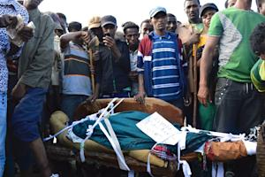 People standing next to the body of a protester from…