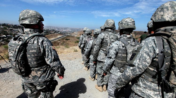 File photo shows National Guard troops standing in formation along the US-Mexico border in San Ysidro, California during a visit by California Gov. Arnold Schwarzenegger on August 18, 2010