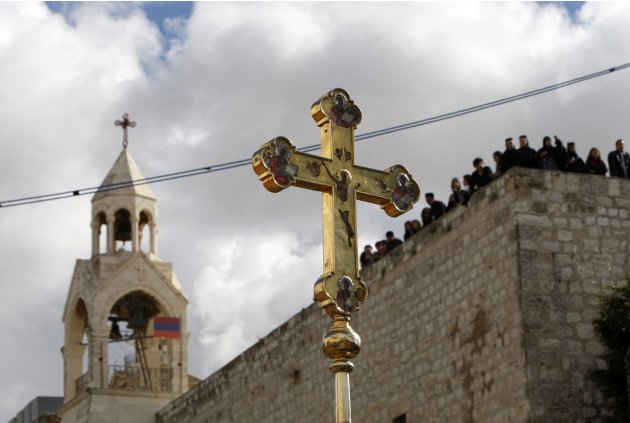 A file photo shows a crucifix held up in front of the Church of the Nativity during the Orthodox Christmas procession in Bethlehem