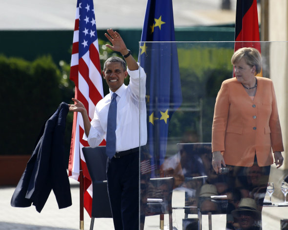 "German Chancellor Angela Merkel watches as U.S. President Barack Obama waves after giving a speech in front of the Brandenburg Gate in Berlin June 19, 2013. Obama's first presidential visit to Berlin comes nearly 50 years to the day after John F. Kennedy landed in a divided Berlin at the height of the Cold War and told encircled westerners in the city ""Ich bin ein Berliner"", a powerful signal that America would stand by them.     REUTERS/Tobias Schwarz (GERMANY  - Tags: POLITICS)"
