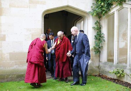 the Dalai Lama (C) arrives for a news conference at Magdalene College ...