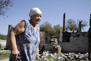 An woman walks beside her ruined house in Pervomayskiy, …