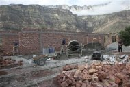 Men build a new madrassa, a religious school, in the village of Gimry, July 9, 2012. REUTERS/Maria Turchenkova