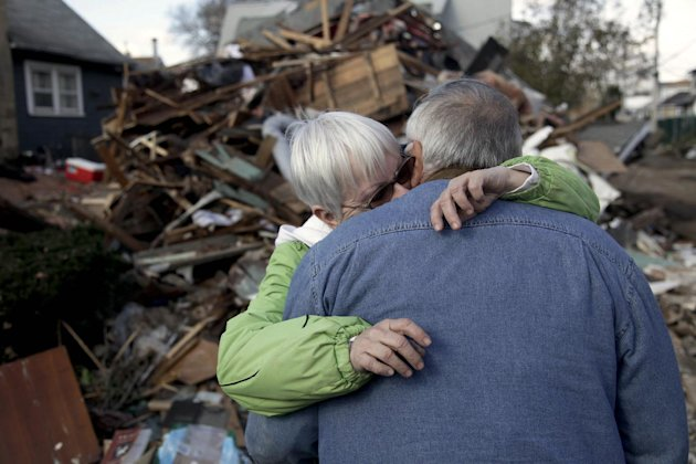 Sheila and Dominic Traina hug in front of their home which was demolished during Superstorm Sandy in Staten Island, N.Y., Friday, Nov. 2, 2012. Mayor Michael Bloomberg has come under fire for pressing ahead with the New York City Marathon. Some New Yorkers say holding the 26.2-mile race would be insensitive and divert police and other important resources when many are still suffering from Superstorm Sandy. The course runs from the Verrazano-Narrows Bridge on hard-hit Staten Island to Central Park, sending runners through all five boroughs. The course will not be changed, since there was little damage along the route. (AP Photo/Seth Wenig)