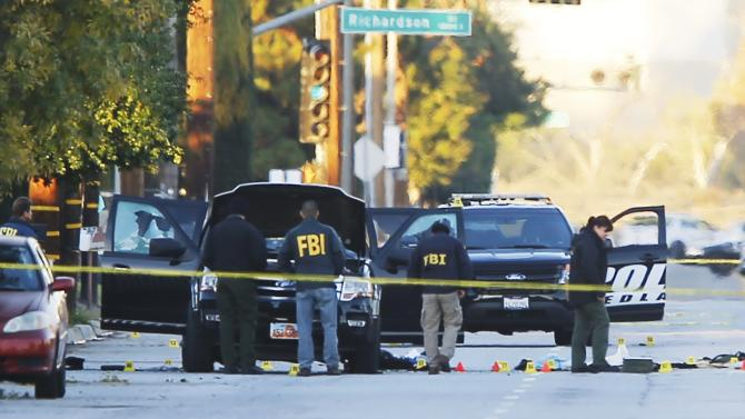 FBI and police investigator are seen around a vehicle in which two suspects were shot following a mass shooting in San Bernardino California