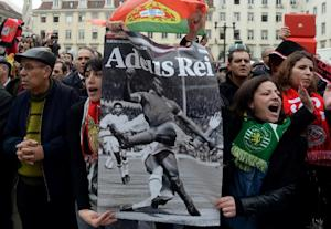 Two women hold a placard depicting Benfica football…