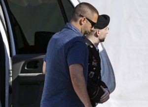 Army Pfc. Bradley Manning, right, is escorted into …